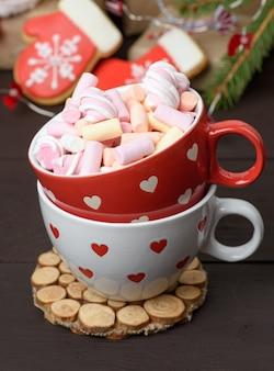 Tazza in ceramica rossa con cacao e marshmallow, dietro una confezione regalo e un giocattolo di natale, da vicino
