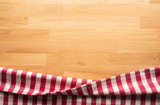 Tessuto a scacchi rosso sul fondo della tavola in legno