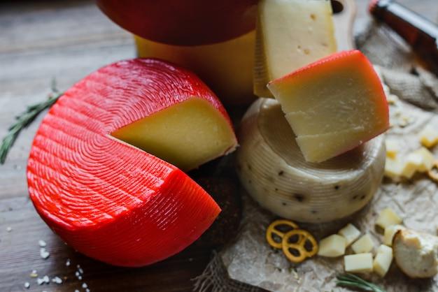 Ruota del formaggio rosso e formaggi assortiti sulla tavola di legno