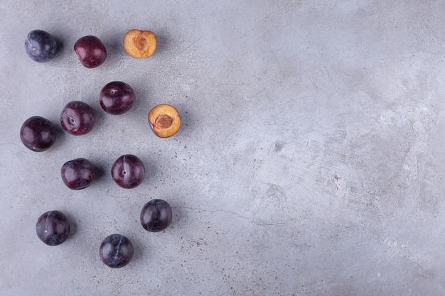Frutti di prugna ciliegia rossa posti su uno sfondo di pietra.