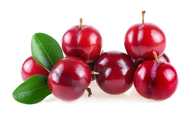Prugna rossa della ciliegia con le foglie verdi isolate su fondo bianco