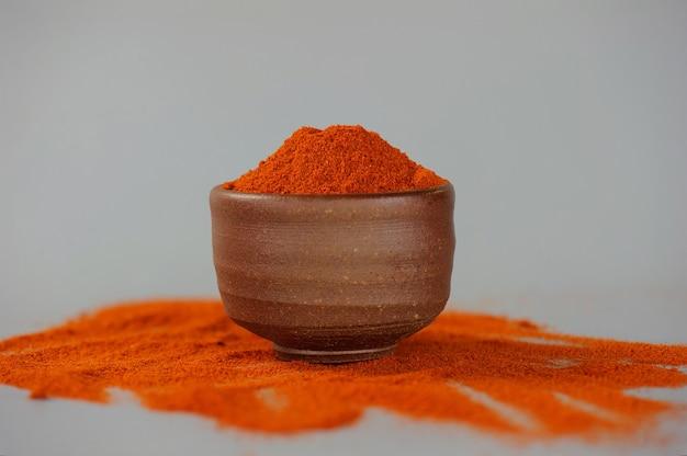 Peperoncino rosso in polvere o paprica in una ciotola di legno su uno sfondo scuro, primo piano. ingredienti da cucina, sapore.