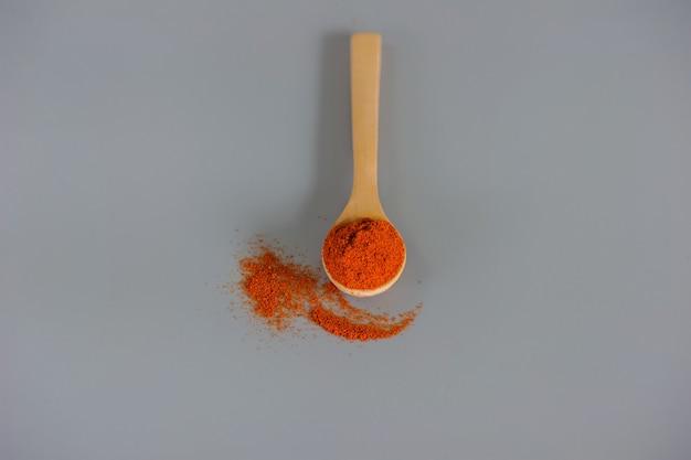 Peperoncino rosso in polvere o paprika in un cucchiaio di legno