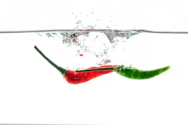 Peperoncino rosso, spruzzi d'acqua, solated su bianco