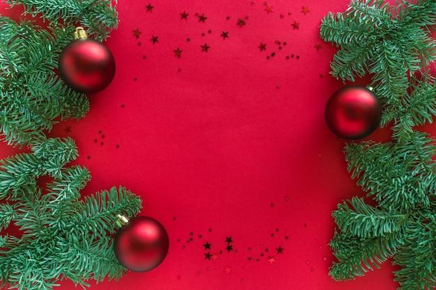 Sfondo rosso di natale decorato con rami di albero, glitter e palline, decorazioni festive di vacanza invernale. buon natale e felice anno nuovo concetto.