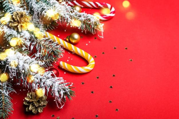 Sfondo rosso di natale con rami di conifere e bastoncino di zucchero.