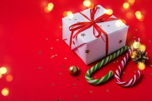 Sfondo rosso di natale con confezione regalo e bastoncino di zucchero.