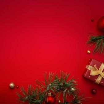 Fondo rosso di natale con l'albero di abete e del regalo sullo spazio della copia.