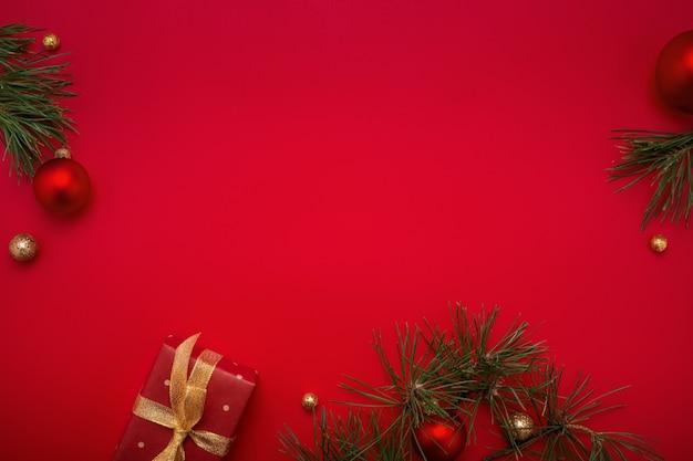 Sfondo rosso di natale con regalo, abete e decorazioni in oro.