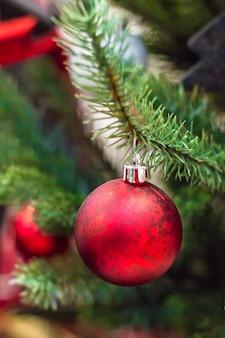 Sfera rossa di natale e fiocco di neve bianco sull'albero di natale