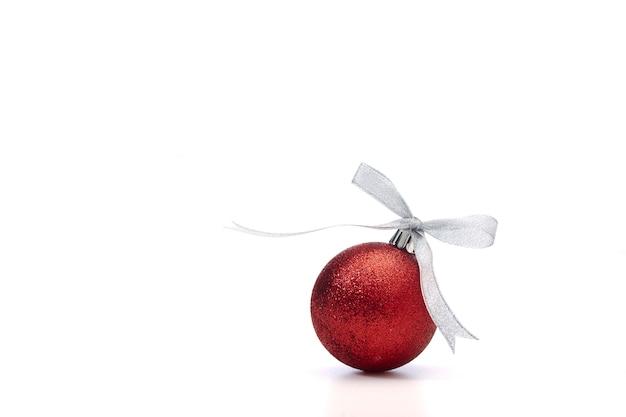 Palla di natale rossa con nastro d'argento su bianco