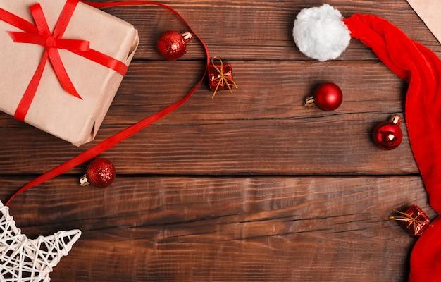Palle di natale rosse sono sparse su uno sfondo di legno marrone, confezione regalo artigianale, cappello babbo natale. lay piatto