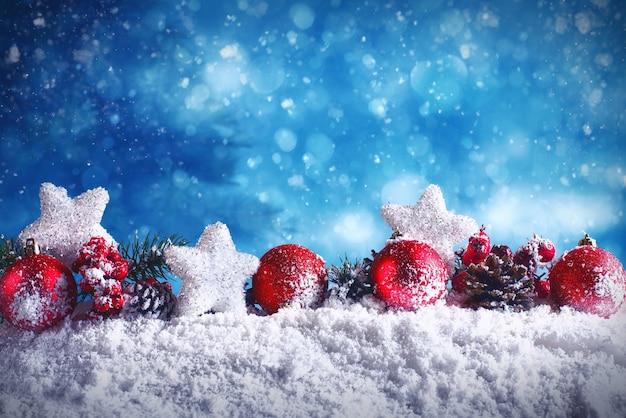 Palle di natale rosse con stelle e ghirlande sulla neve