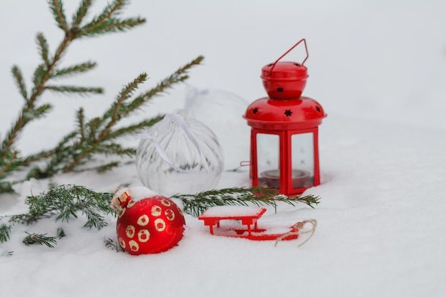 Bagattella rossa di natale che appende su una filiale del pino nevoso in inverno