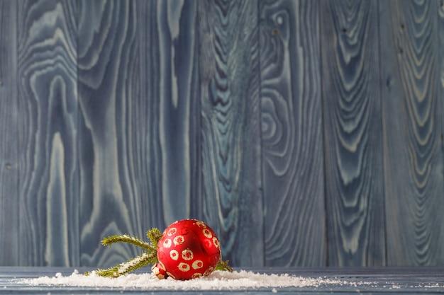 Decorazioni rosse di natale sui rami attillati con neve