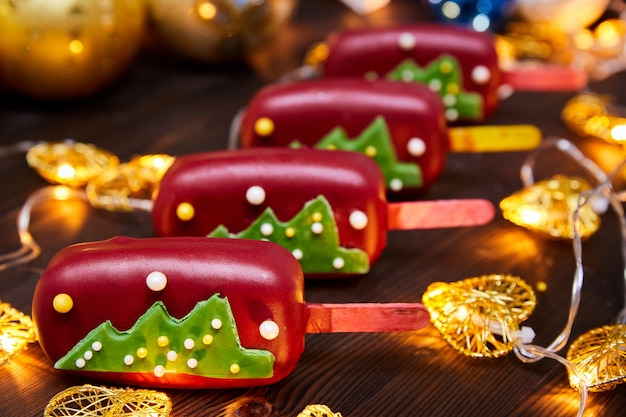 Dolce natalizio rosso a forma di mousse su stecco decorato con albero di natale