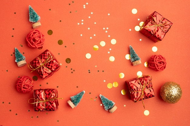 Regali di natale rossi e alberi di natale su sfondo rosso. un articolo sul capodanno e il natale. la scelta dei regali. un regalo rosso.