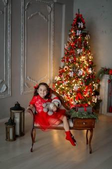 Foto rossa di natale della bambina sul sofà con un regalo in sue mani.