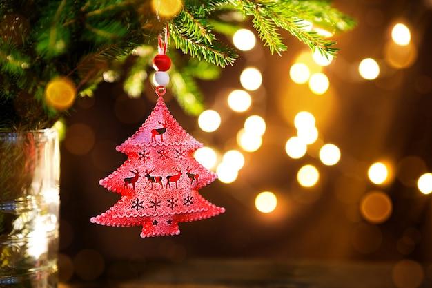 Giocattolo rosso dell'albero di natale su un ramo di un abete naturale con luci di ghirlande sfocate sullo sfondo. giocattolo in metallo con fessure di cervo e fiocchi di neve. natale, capodanno, copia spazio, bokeh.