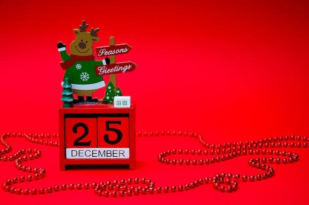 Calendario di legno rosso di natale con un cervo su uno sfondo rosso data 25 dicembre