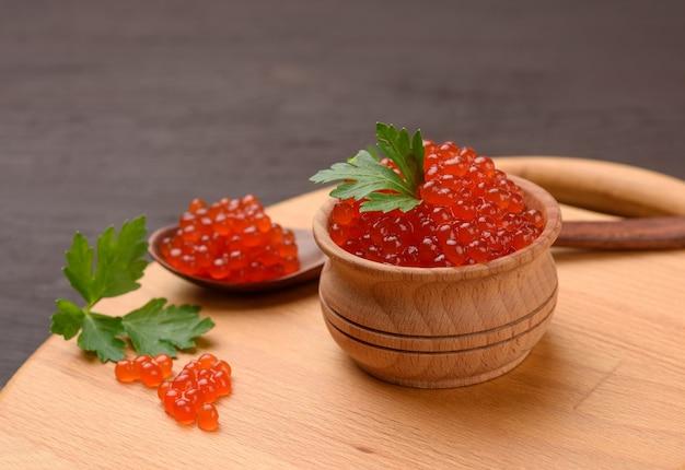 Caviale di salmone rosso chum in una ciotola di legno, cibo delizioso e sano, primi piani