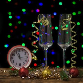 Orologio rosso e bicchieri di champagne decorati su una decorazione festiva. anno nuovo concetto