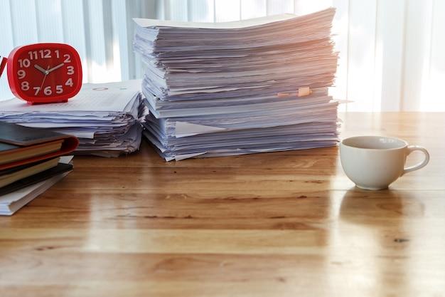 Orologio e articoli per ufficio rossi sullo scrittorio in ministero degli interni al mattino, tono caldo