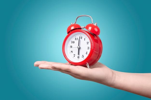 Orologio rosso con sveglia a portata di mano su sfondo blu, sveglia il concetto al mattino