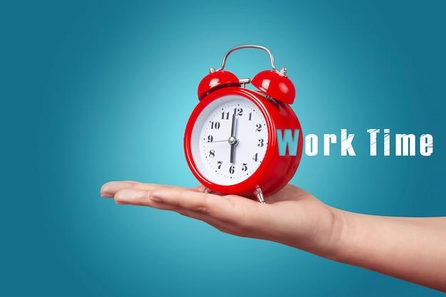 Orologio rosso con sveglia a portata di mano su sfondo blu, concetto di tempo di lavoro