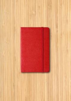 Taccuino chiuso rosso isolato su superficie di legno