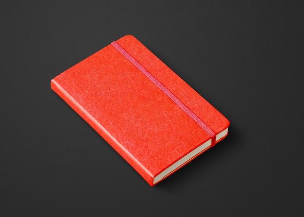 Modello di taccuino chiuso rosso isolato su nero