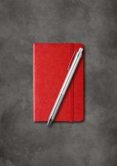 Taccuino chiuso rosso con una penna. isolato su sfondo scuro di cemento