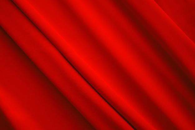 Fondo rosso del panno. decorazione onda trama liscia tessuto display carta da parati di lusso sullo sfondo. spazio libero per aggiungere testo o prodotti. per natale o felice anno nuovo, concetto di tecnologia.