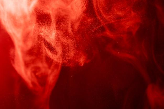 Nuvola di fumo rossa di fondo isolato nero. sfondo dal fumo di vaporizzatore