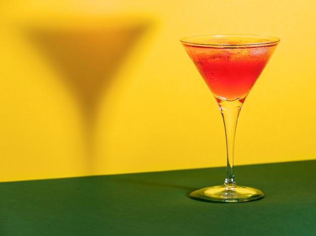 Cocktail rosso in un bicchiere che modella la sua ombra