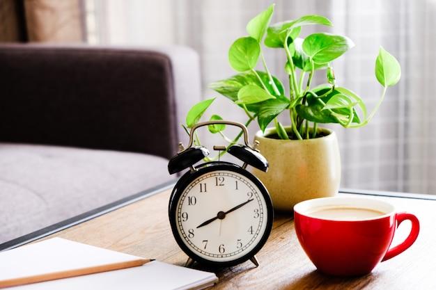 Una tazza di caffè rossa, un orologio nero posto su un tavolo con un vaso di fiori e un libro su di esso.
