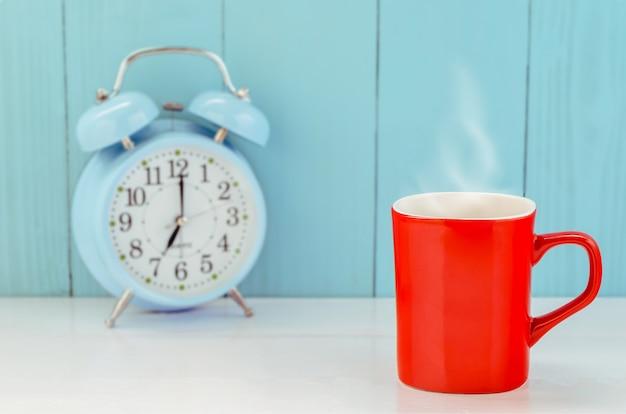 Tazza da caffè rossa sul tavolo di legno