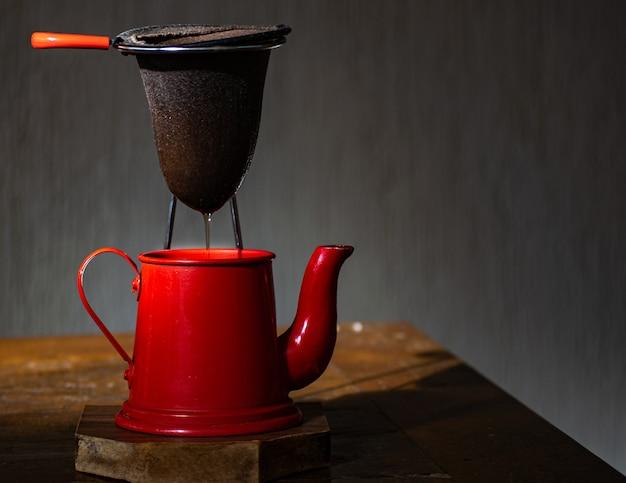 Caffettiera rossa e colino di stoffa, con sfondo scuro