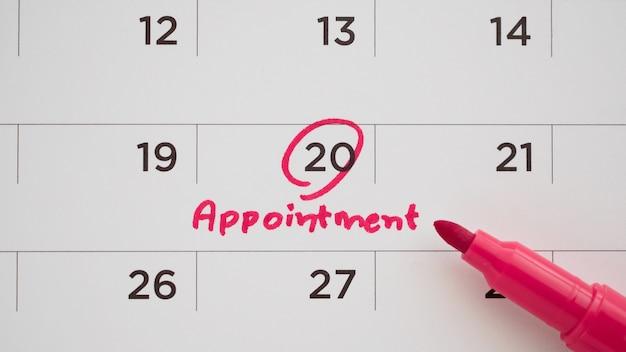 Pennarello di colore rosso che punta a un appuntamento importante sulla data del calendario