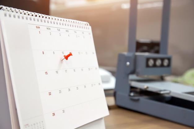 Un perno di colore rosso sul calendario, concetto per il pianificatore di eventi.