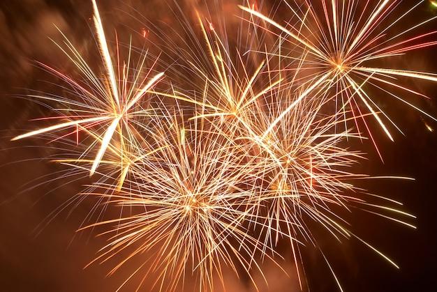 Fuochi d'artificio colorati rossi sui precedenti del cielo nero. celebrazione delle vacanze.