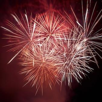 Fuochi d'artificio colorati rossi sui precedenti del cielo nero.