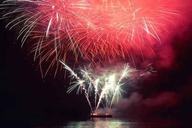 Fuochi d'artificio colorati rossi di festa sui precedenti del cielo nero.