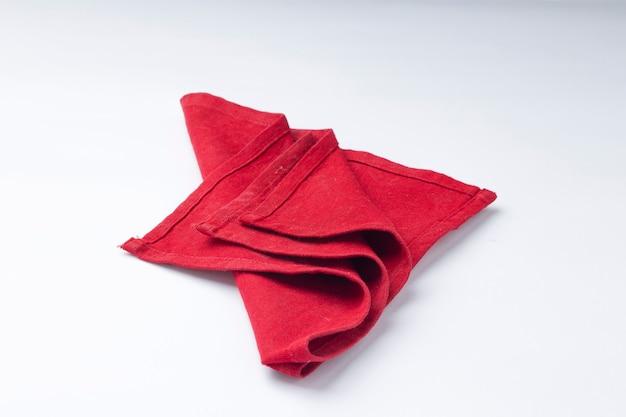 Tovagliolo di colore rosso disposto su sfondo bianco a trama, fuoco isolato e selettivo.