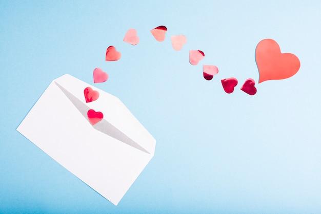 Cuori di coriandoli rossi volano fuori da una busta bianca su un tavolo azzurro. san valentino. concetto di amore regalo, messaggio per l'amante.