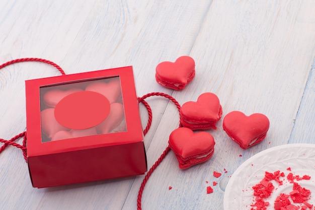 Biscotti rossi a forma di cuore in una confezione regalo su tavole di legno con nastro il giorno di san valentino