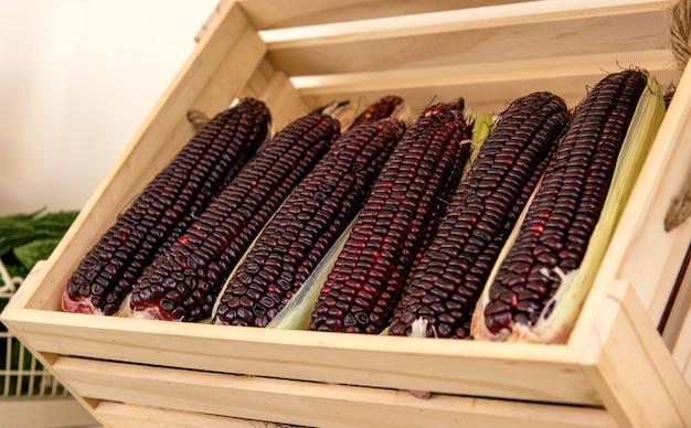 Frutti di mais rosso sul fondo della natura.