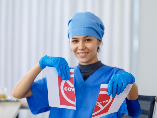 Il segno di carta rosso covid-19 è stato fatto a pezzi da un bel dottore felice in uniforme ospedaliera blu su sfondo sfocato quando la pandemia di coronavirus è terminata e la vita normale e la sicurezza degli affari sono aperte.