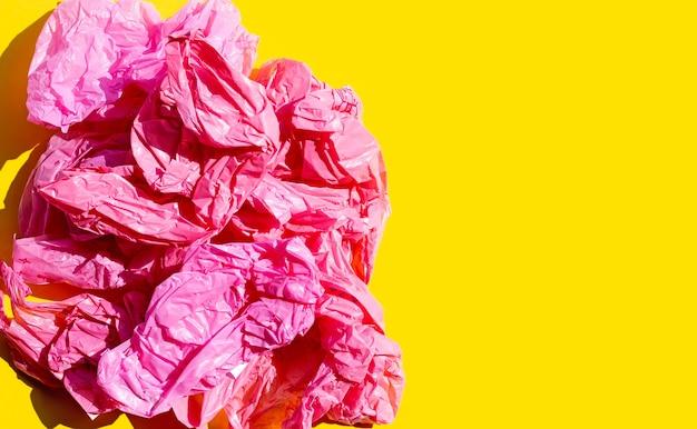 Sacchetti di plastica sgualciti rossi sulla superficie gialla
