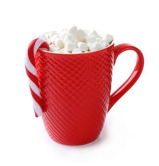 Una tazza rossa di cacao, marshmallow e caramelle natalizie, isolata su bianco